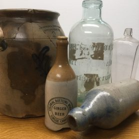 Collection of cracked and/or broken bottles, stoneware pots, etc.