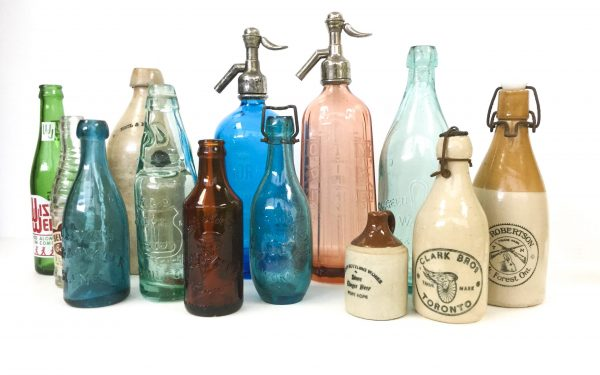 Collection of colourful glass and stoneware soda bottles