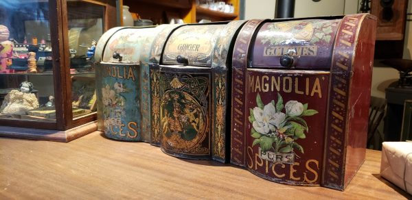 Three hand-painted rectangular spice tins in with curved lids sitting on wooden counter in the General Store display.