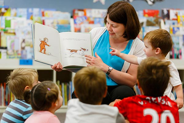 Woman in library setting reading a picture book to five young children.