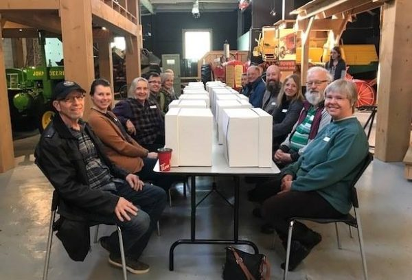 Potential volunteers sitting at two long, rectangular tables. On the table in front of each person is a white cardboard box with a mystery item inside.